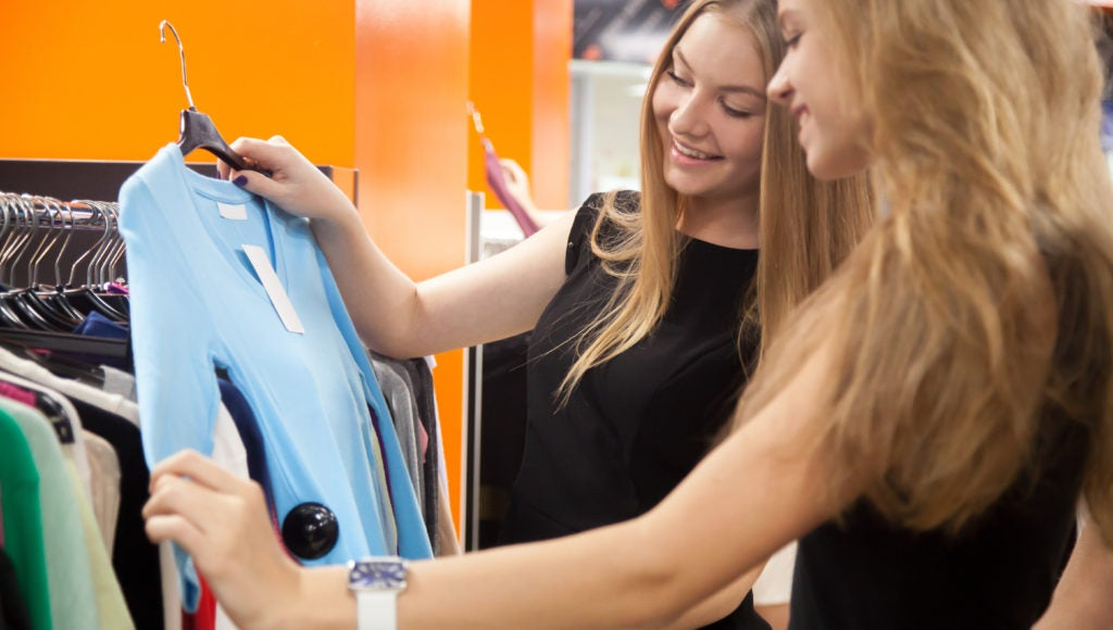 A retail associate helping a customer select clothing