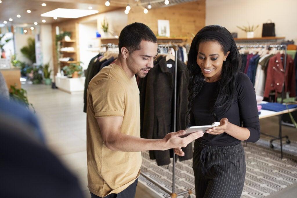 Retail associate helping customer using technology
