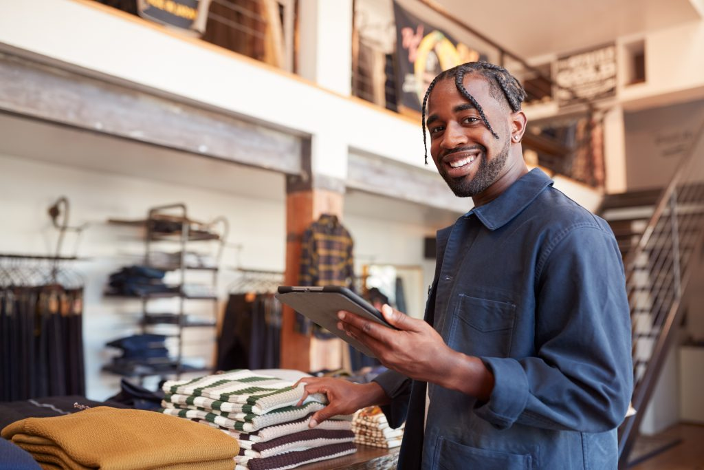 Owner Of Fashion Store Using Digital Tablet